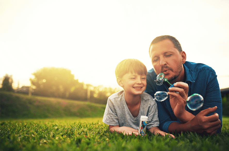 man with son blowing bubbles