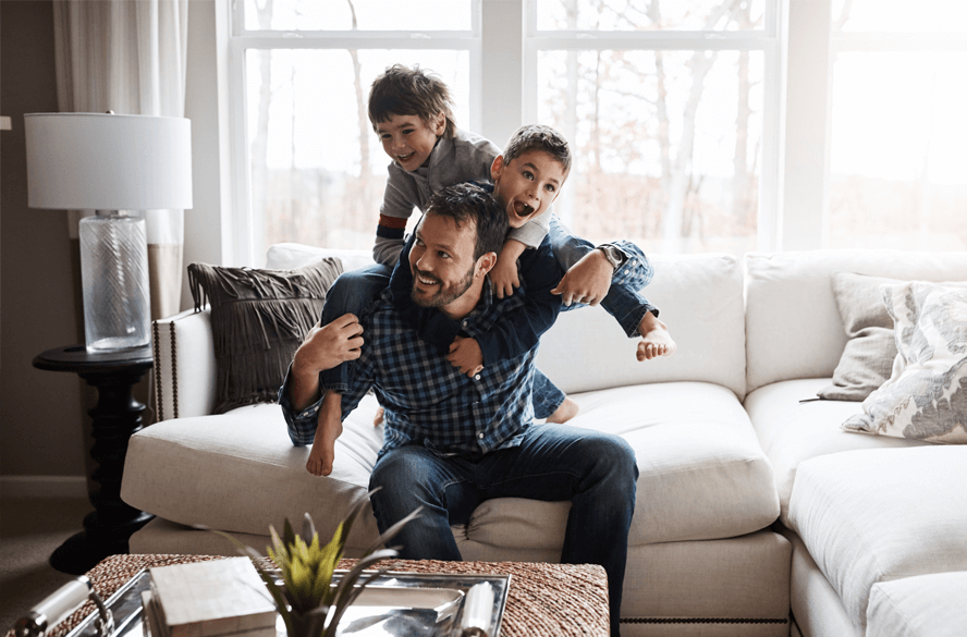 man with two sons on couch